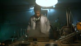 Dziwaczny naukowiec otwiera stalowego pudełko z składnikami zbiory