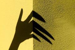 Dziwaczny ręka cień na żółtej kamiennej ścianie Czarny cie?, ?e?ska r?ka obraz royalty free