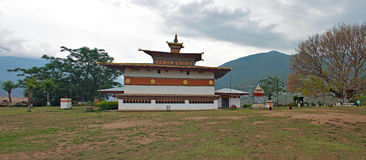 A Dzong in Bhutan. Chimi Lhakhang or Fertility Temple is a Dzong (Buddhist Monastery) near Punakha, Bhutan. Dzong typically houses monks. A huge Peepal/sacrate Royalty Free Stock Image