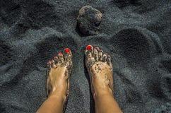Żeńscy nadzy cieki z czerwonymi gwoździami na czarnym piasku wyrzucać na brzeg Fotografia Stock
