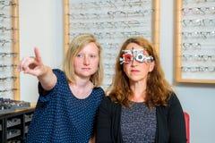 Żeńscy optican sprawdza oczy kobieta dla nowych szkieł Obrazy Stock