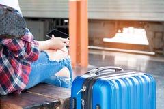 Żeńscy podróżnicy bawić się mądrze telefony podczas gdy czekający pociągów wi Fotografia Stock