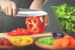 Żeńscy tnący czerwoni dzwonkowi pieprze Kulinarny weganinu jedzenie zdrowy dowcip fotografia royalty free