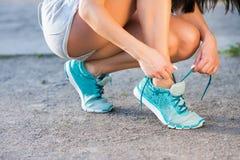 Żeńska atleta jest ubranym w szarość zwiera, wiążący błękitnego sporta obuwie Zdjęcie Royalty Free