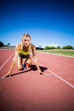 Żeńska atleta przygotowywająca bieg na bieg śladzie obraz stock