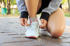 Żeńska atleta wiąże koronki dla jogging na drodze Obrazy Stock