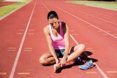Żeńska atleta z stopa bólem na bieg śladzie obrazy stock
