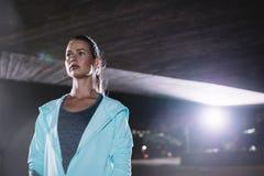 Żeńska biegacz pozycja pod mostem przy nocą Obraz Stock
