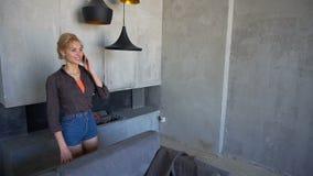 Żeńska blondynka mówi na komórkowym i chodzi wokoło żywego pokoju, uśmiechnięty i roześmiany, siedzi na plecy kanapa zbiory wideo