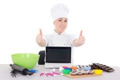 Żeńska cukierniczka w kucharza munduru obsiadaniu przy kuchnią z Obrazy Royalty Free