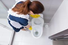 Żeńska domowego pracownika czyści biała toaleta Zdjęcia Stock