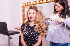 Żeńska fryzjer pozycja i robić śliczna urocza młoda kobieta fryzura Zdjęcie Stock