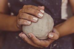 Żeńska garncarka wręcza chwyt glinę dla garncarstwa, selekcyjna ostrość Fotografia Royalty Free