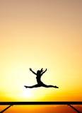 Żeńska gimnastyczka na balansowym promieniu w zmierzchu Obrazy Stock