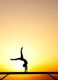 Żeńska gimnastyczka na balansowym promieniu w zmierzchu Fotografia Stock