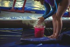 Żeńska gimnastyczka stosuje kreda proszek na jej rękach przed ćwiczyć obrazy royalty free