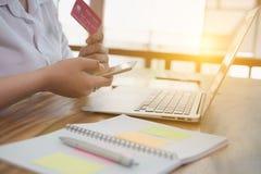Żeńska kobieta trzyma kredytową kartę i używa telefon komórkowego dla dalej Obrazy Royalty Free