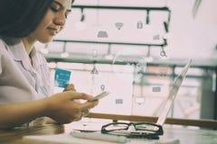 Żeńska kobieta trzyma kredytową kartę i używa telefon komórkowego dla dalej Fotografia Royalty Free