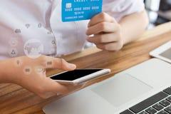 Żeńska kobieta trzyma kredytową kartę i używa telefon komórkowego dla dalej Zdjęcia Stock