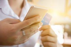 Żeńska kobieta trzyma kredytową kartę i używa telefon komórkowego dla dalej Obrazy Stock