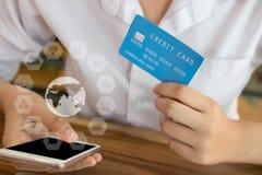 Żeńska kobieta trzyma kredytową kartę i używa telefon komórkowego dla dalej Obraz Stock