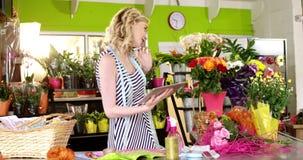 Żeńska kwiaciarnia bierze rozkaz na telefonie komórkowym zbiory