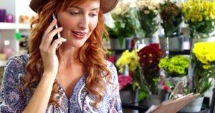 Żeńska kwiaciarnia bierze rozkaz na telefonie komórkowym zdjęcie wideo