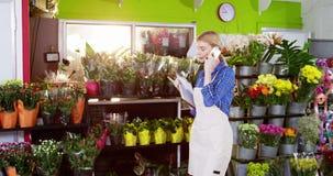 Żeńska kwiaciarnia bierze rozkaz na telefonie komórkowym w kwiatu sklepie zbiory