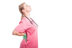 Żeńska medyczna pielęgniarka trzyma ona jak kaleczenie z powrotem obraz stock