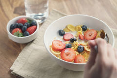 Żeńska nastoletnia dziewczyny ręka je zdrowego śniadanie z kukurydzanymi płatkami i jagodami zdjęcia royalty free