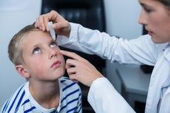 Żeńska optometrist kładzenia oka kropla w młodych cierpliwych oczach obrazy royalty free