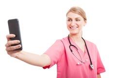 Żeńska pielęgniarka jest ubranym pętaczki bierze selfie z smartphone obraz royalty free