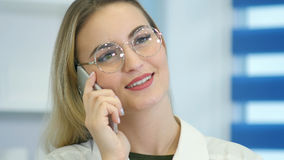 Żeńska pielęgniarka przy szpitalnym przyjęciem opowiada na telefonie Obrazy Royalty Free