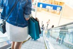 Żeńska pozycja na eskalatorów wydatków klienta konsumeryzmu przy wydziałowym sklepem Zdjęcia Stock