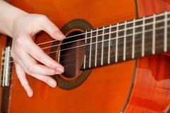 Żeńska ręka bawić się gitarę akustyczną Zdjęcia Royalty Free