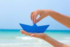 Żeńska ręka bawić się z papierową łodzią w wodzie na plaży Zdjęcia Stock