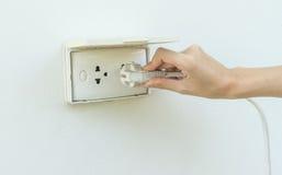 Żeńska ręka czopuje w urządzeniu elektryczny ujście w ścianie o Fotografia Stock