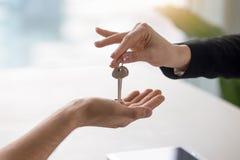 Żeńska ręka daje kluczom męski klient, kupuje wynajmowania mieszkanie Zdjęcia Stock
