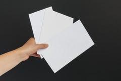 Żeńska ręka dostarcza 3 koperty na czarnym tle Obraz Royalty Free