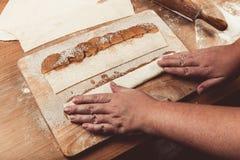 Żeńska ręka kropi jabłczanych plasterki na ciasto pasku na świetle Obrazy Stock