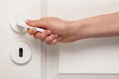 Żeńska ręka na drzwiowej rękojeści Obrazy Stock