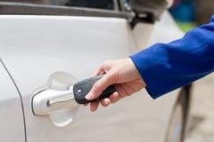 Żeńska ręka otwiera białego samochód na kluczowym systemu automatycznym Zdjęcia Stock