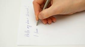 Żeńska ręka pisze Mnie kocha ciebie na papierowym prześcieradle obraz stock