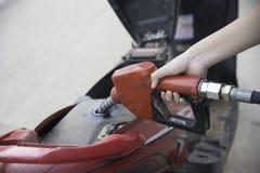Żeńska ręka refilling motocykl z paliwem na plombowania stat Obrazy Royalty Free
