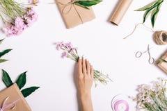 Żeńska ręka stawia bukiet różowi kwiaty na stole Obraz Stock