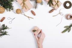 Żeńska ręka stawia pudełko z prezentem na stole z Bożenarodzeniowym b Obrazy Stock