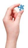 Żeńska ręka trzyma błękitnego łamigłówka kawałek obrazy royalty free