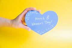 Żeńska ręka trzyma błękitnego papier kierowy na złotym tle - Szczęśliwy kobiety ` s dzień Obrazy Royalty Free