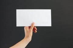 Żeńska ręka trzyma białą kopertę na czarnym tle Obrazy Royalty Free