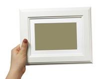 Żeńska ręka trzyma drewnianą ramę odizolowywająca na białym tle zdjęcia stock